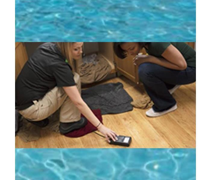 Two women metering wet flooring