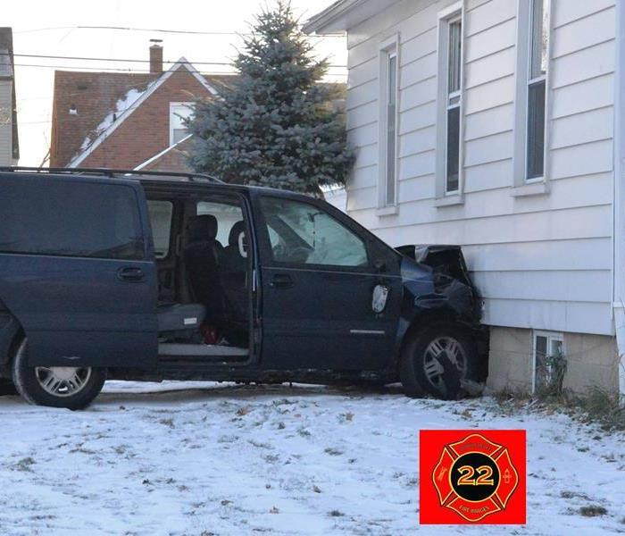 Blue car crashed into side of house after slipping off icy road