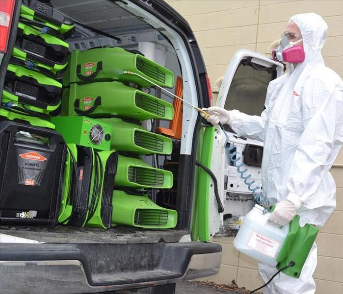 Technician in biohazard suit sanitizing equipment